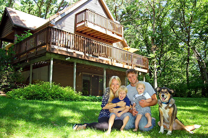 Dog with family in front of new home